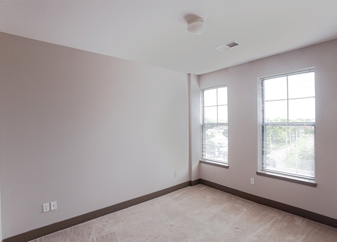 White, carpeted room with large windows