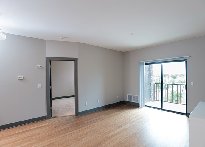 Open room with wood floors, a sliding glass door and a balcony