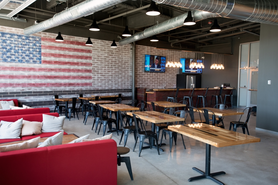game day viewing area show tables with American flag on wall