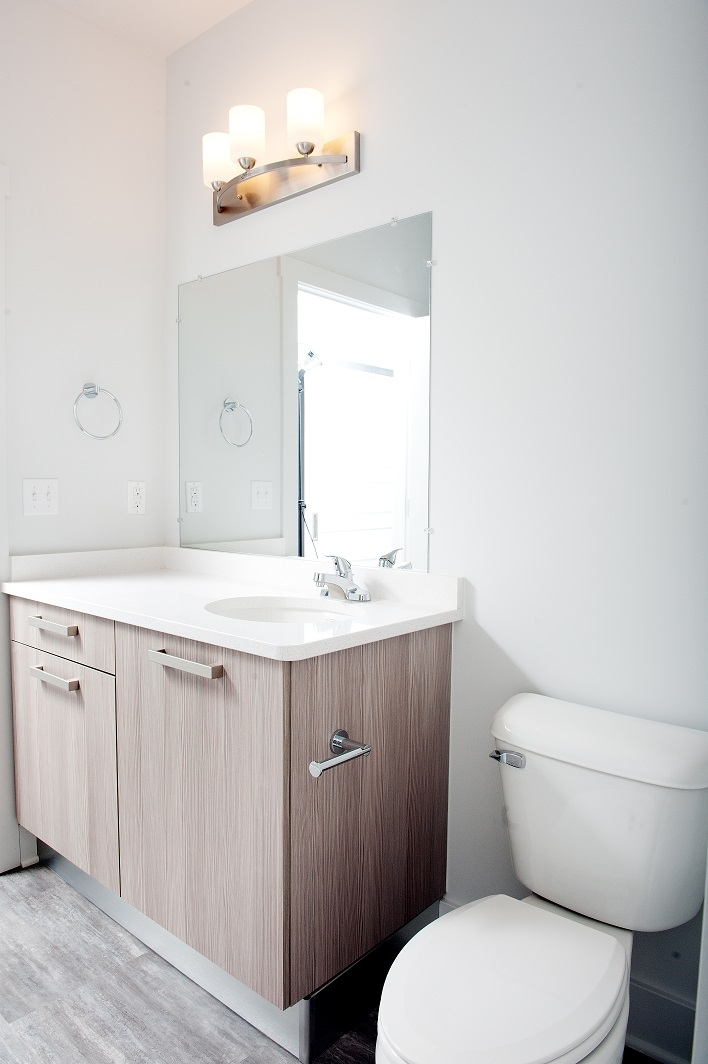 bathroom with white walls, mirror white counter and wood cabinets
