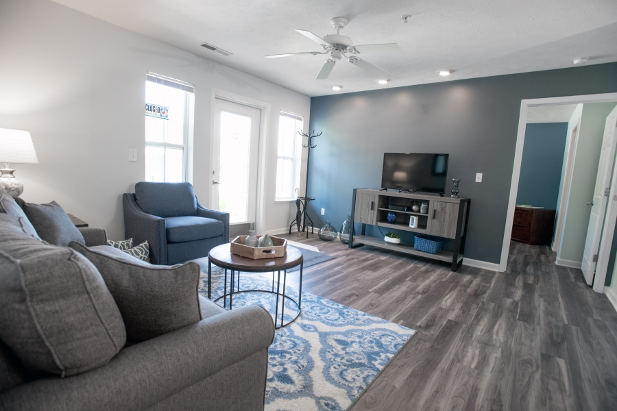 iiving room with grey coach, wood floors and white and gray wall